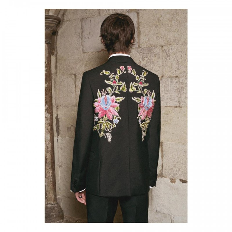 A tailored jacket embellished with embroidered patches on the back