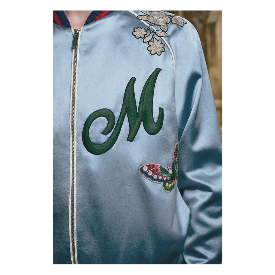 An embroidered patch letter on the chest of a silk bomber jacket with stripe Web trim.