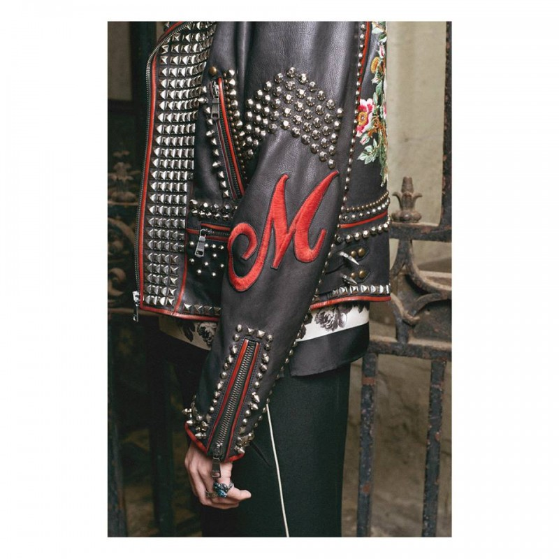 On a studded leather jacket, an embroidered patch letter is positioned on the sleeve