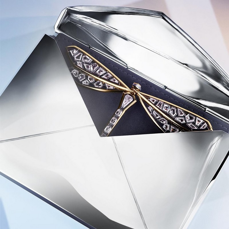 A dragonfly takes flight from an angular sterling silver envelope with wings constructed from custom-cut diamonds