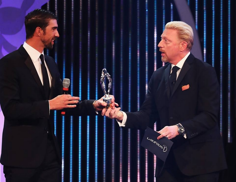 Swimmer Michael Phelps of the US accepts his award from Laureus Academy member Boris Becker