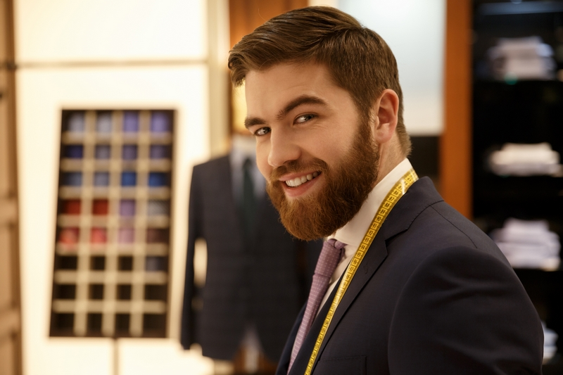 Portrait of cheerful man in suit in cloakroom