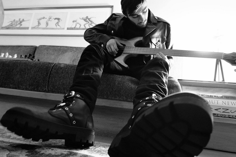 ZaynMalik playing guitar in a Versus biker leather jacket